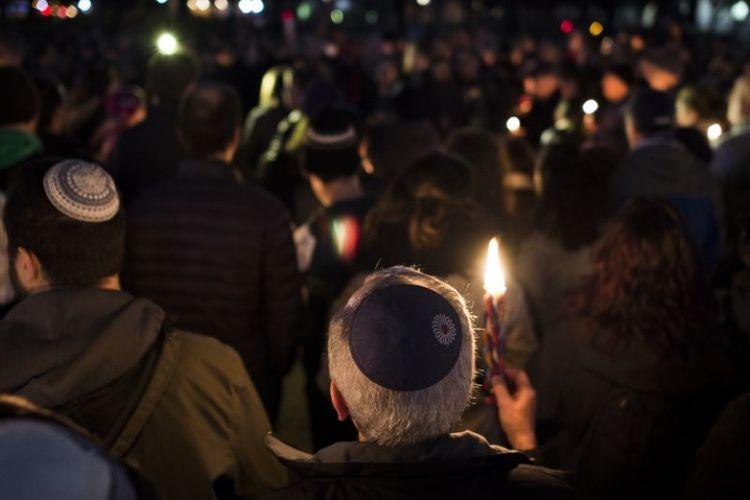 Anggota dan pendukung komunitas Yahudi menyalakan lilin untuk menghormati korban penembakan di sinagoge Tree of Life Synagogue di lingkungan Squirrel Hill di Pittsburgh. Mereka berkumpul di depan Gedung Putih di Washington DC pada Sabtu (27/10/2018). (AFP/Andrew Caballero-Reynolds)