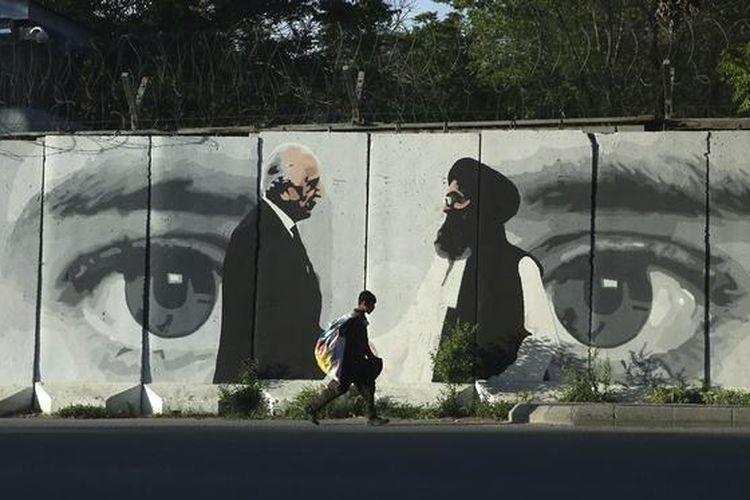 Seorang bocah melintasi mural yang menggambarkan Zalmay Khalilzad (kiri), utusan damai dari Washington dan Mullah Abdul Ghani Barada (kanan) kepala delegasi Taliban, di Kabul (5/5/2020).