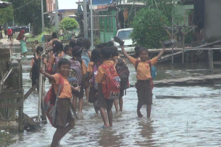 Banjir yang merendam jalan Desa Ibul Besar 1 Kecamatan Pemulutan membuat siswa sekolah dasar setempat harus melintasi banjir dengan cara membuka sepatu dan berjalan di dalam air banjir. Menurut mereka sudah seminggu ini mereka harus menjalani situasi seperti itu
