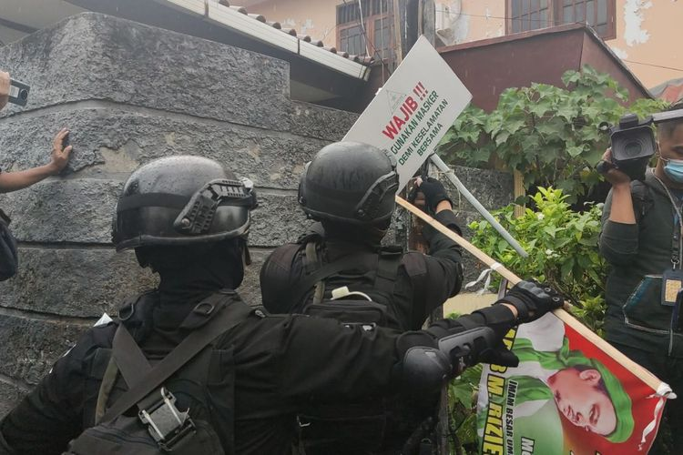 Military and police personnel take down FPI banners, posters and other images following the groupss disbanding on Wednesday (30/12/2020)