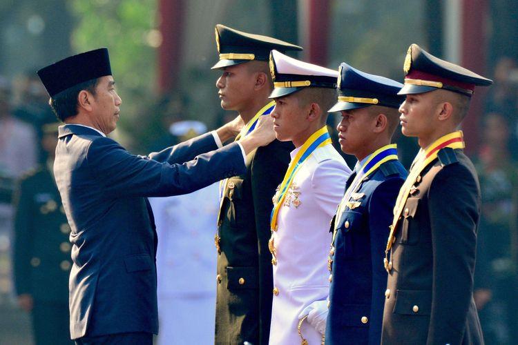 Presiden Joko Widodo saat memberikan penghargaan Adhi Makayasa kepada lulusan terbaik dari Akmil, AAL, AAU, dan Akpol di halaman Istana Merdeka, Jakarta, Selasa (16/7/2019). Presiden Joko Widodo melantik 781 perwira TNI-Polri yang terdiri atas 259 perwira TNI AD, 117 perwira TNI AL, 99 perwira TNI AU dan 306 perwira Polri.