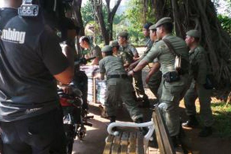 Petugas Satpol PP menyita barang dagangan dari PKL di Monas yang disembunyikan pedagang di semak taman. Sabtu (2/8/2014).