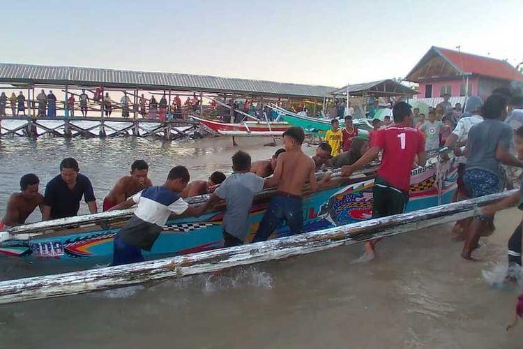 Para warga ketika menarik kapal milik nelayan Kodingareng Lompo yang diduga hendak ditenggelamkan di perairan Kodingareng Makassar, Minggu (23/8/2020).