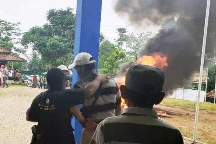 Warga menyaksikan aksi pembakaran yang dilakukan sekelompok massa yang memprotes hasil tahapan seleksi pilkades di Desa Waringinsari, Kabupaten Cianjur, Jawa Barat, kemarin.