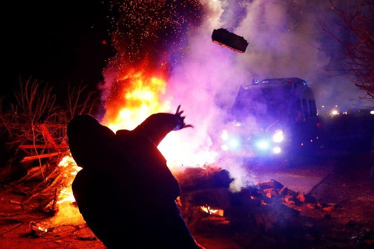 Seorang demonstran melempar batu ke arah van polisi ketika terlibat bentrok desa Novi Sanzhary, Region Poltava, Ukraina pada 20 Februari 2020. Massa menolak warga yang dievakuasi dari China karena takut tertular virus corona.