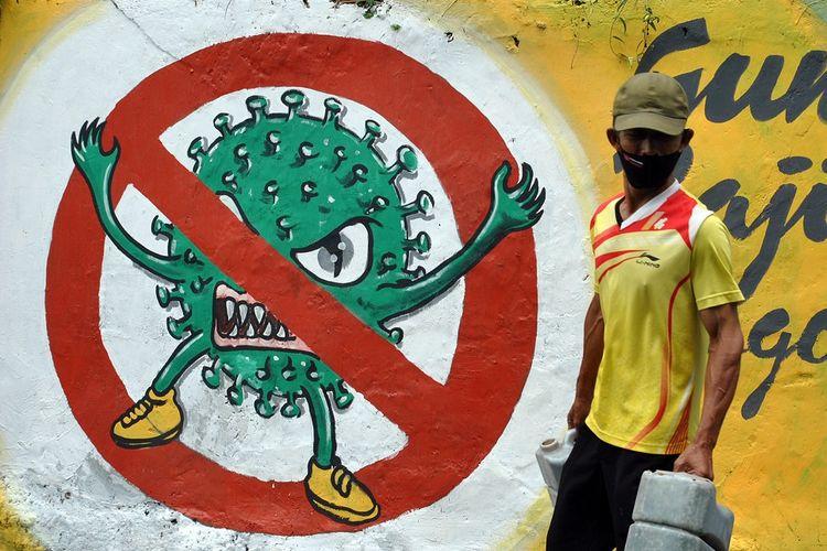 Warga menggunakan masker berjalan di samping mural bergambar COVID-19 di jalan Roda 2 Gang Mesin RT 01/01, Kelurahan Babakan Pasar, Kota Bogor, Jawa Barat, Minggu (11/10/2020). Mural dalam bentuk himbauan protokol kesehatan pencegahan dan penyebaran COVID-19 tersebut untuk mengingatkan warga bahwa Kota Bogor masih berada dalam zona merah atau risiko tinggi penyebaran COVID-19 dengan kumulatif kasus positif sebanyak 1.511 pasien. ANTARA FOTO/Arif Firmansyah/foc.