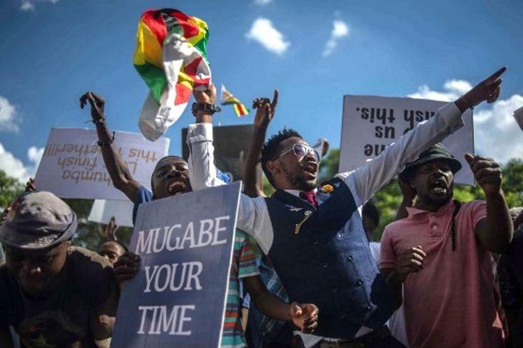 Warga Zimbabwe bersukacita menyambut pengunduran diri Robert Mugabe dari kursi kepresidenan Zimbabwe, Selasa (21/11/2017). (AFP/Mujahid Safodien)