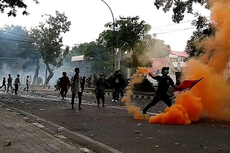 Seorang massa aksi melempar balik gas air mata yang dilesatkan ke arah polisi saat aksi unjuk rasa  yang sempat berlangsung rusuh di DPRD Sumut pada Kamis (8/10/2020).