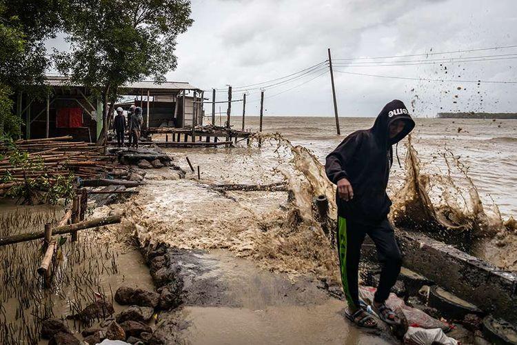 Warga menembus jalan desa yang rusak akibat terjangan gelombang tinggi air laut di Desa Bedono, Sayung, Demak, Jawa Tengah, Senin (7/12/2020). BMKG mengeluarkan peringatan dini gelombang tinggi setinggi 2,5 - 4 meter dengan kecepatan angin 30 knot yang berpeluang terjadi pada Senin (7/12) - Rabu (9/12) di sejumlah wilayah perairan dan pesisir di Indonesia di antaranya yaitu laut Jawa bagian tengah, dengan imbauan kepada nelayan maupun warga yang bermukim di daerah tersebut agar waspada saat beraktivitas.