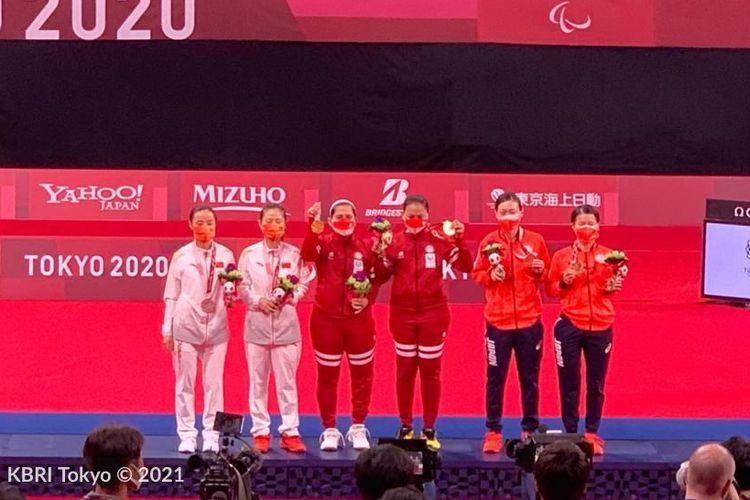 Leani Ratri Oktila/Khalimatus Sadiyah berdiri di podium usai meraih medali emas Paralimpiade Tokyo 2020.