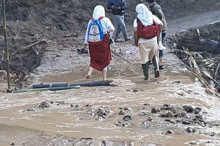 Siswa SD korban terdampak longsor saat melewati jalan yang baru dibuka setelah tertutup material longsoran di Desa Santanamekar Kecamatan Cisayong Kabupaten Tasikmalaya, Kamis (5/3/2020).