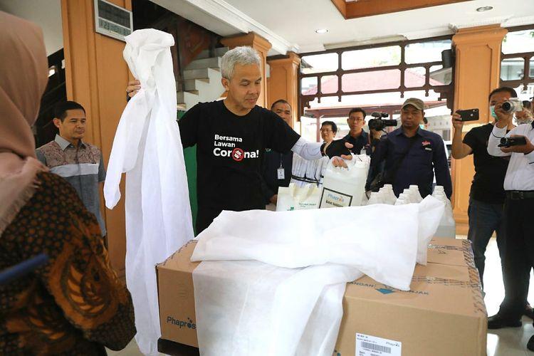 Gubernur Ganjar Pranowo menunjukkan pakaian Alat Pelindung Diri di kantor Dinas Kesehatan Jawa Tengah, Senin (23/3/2020).