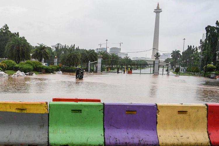Warga mendorong motor melintasi banjir di kawasan Monas, Jalan Medan Merdeka Barat, Jakarta, Minggu (2/2/2020). Hujan deras yang mengguyur Jakarta pada Minggu (2/2) pagi menyebabkan beberapa ruas jalan di ibu kota tergenang banjir dengan ketinggian 10-50 centimeter.