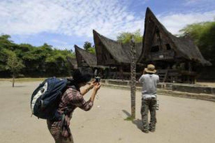 Anggota tim Ekspedisi Cincin Api Kompas mendokumentasikan kawasan rumah adat Batak di Huta Bolon, Kecamatan Simanindo, Kabupaten Samosir, Sumatera Utara, Sabtu (23/7/2011).