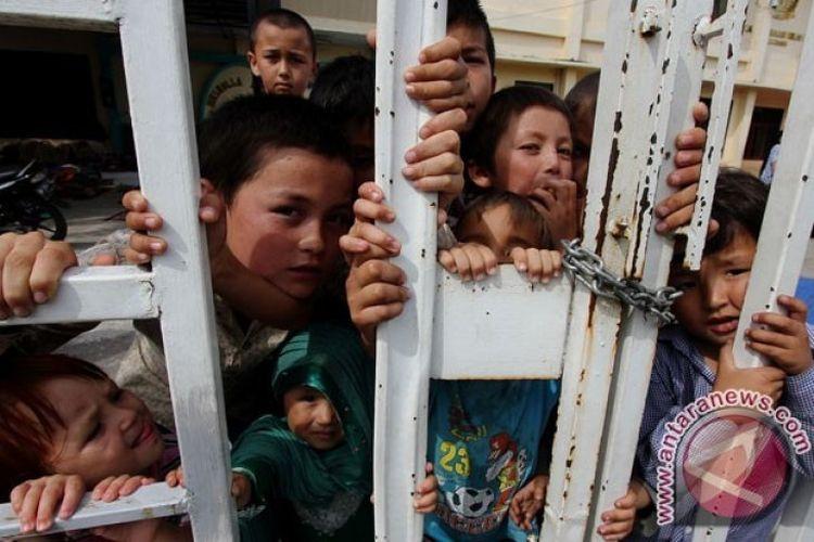 Arsip Foto. Anak-anak imigran asal Afghanistan berdiri di pagar pembatas Kantor Imigrasi Pekanbaru, Riau, Rabu (15/6/2016)