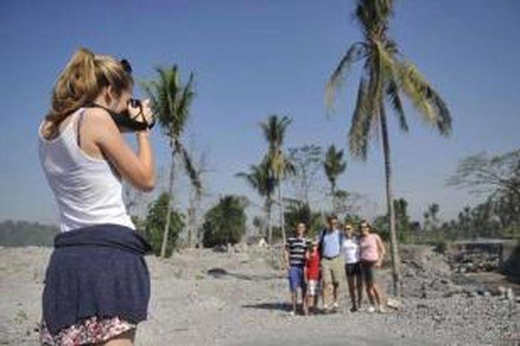 Wisatawan asal Belanda mengabadikan kunjungan mereka di permukiman yang rusak terkena lahar hujan di Desa Jumoyo, Salam, Magelang, Jawa Tengah, Rabu (6/7/2011). Lokasi tersebut menjadi salah satu tempat singgah bagi berbagai agen pariwisata Yogyakarta yang hendak mengantar wisatawan ke Candi Borobudur.