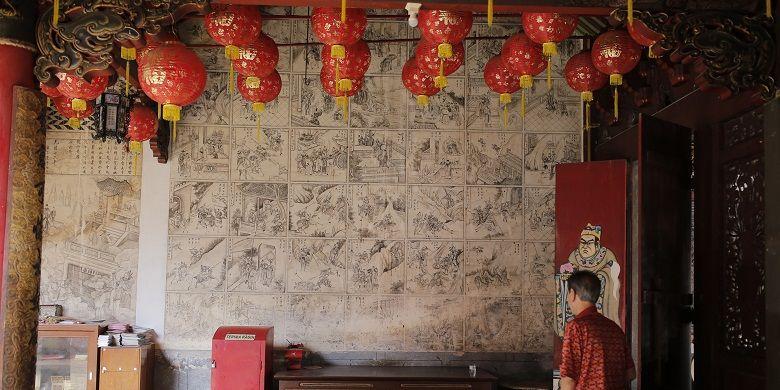 Salah satu pengunjung melihat panel-panel mural Klenteng Cu Ang Kiong yang terletak di Desa Dasun, Kecamatan Lasem, Kabupaten Rembang, Jawa Tengah, Minggu (12/2/2017). Mural monokrom hitam putih itu berasal dari 100 panel 'komik' Fengshen Yanyi dikenal juga dengan nama Fengshenbang atau Kisah Mitologi Dewa-Dewa Taois karya Xu Zhonglin. Fengshen Yanyi ditulis pada masa Dinasti Ming (1368-1644) dan diterbitkan pada tahun 1550.