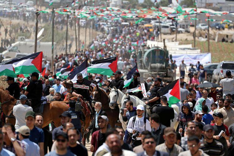 Warga Palestina berkumpul saat aksi protes memperingati 71 tahun Nakba, atau malapetaka, ketika ratusan ribu mereka dipaksa meninggalkan rumah di tengah perang yang mengelilingi kemerdekaan Israel pada 1948, dekat perbatasan Israel-Gaza, bagian timur Kota Gaza, Rabu (15/5/2019).