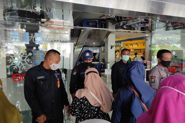 MASUK MALL—Pengunjung yang masuk ke Plaza Mall Kota Madiun menunjukkan aplikasi peduli lindungi kepada petugas, Rabu (8/9/2021).