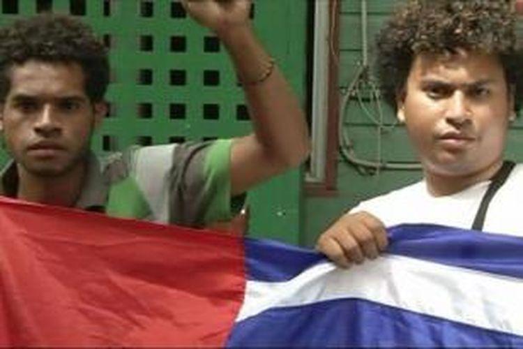 Dua orang aktivis Papua Barat difoto sambil memegang bendera Papua Barat di Papua Niugini.
