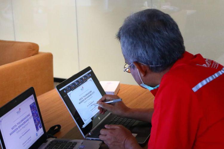 Direktur Network & IT Solution Telkom Zulhelfi Abidin menandatangani prasasti digital peresmian Modern City Kediri dan Tulungagung melalui video conference di Jakarta, Rabu (29/04/2020).