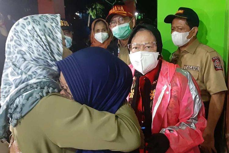 Menteri Sosial Tri Rismaharini berbincang dengan istri korban meninggal dunia akibat tertimbun longsor di Cimanggung, Sumedang, Jawa Barat, Minggu (10/1/2021) malam. AAM AMINULLAH/KOMPAS.com