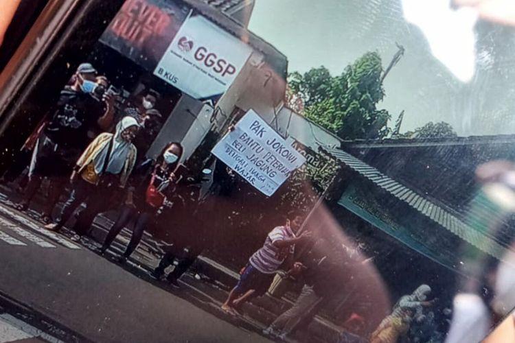 Seorang pria membentangkan poster di depan mobil Presiden Jokowi di Kota Blitar, Selasa (7/9/2021)
