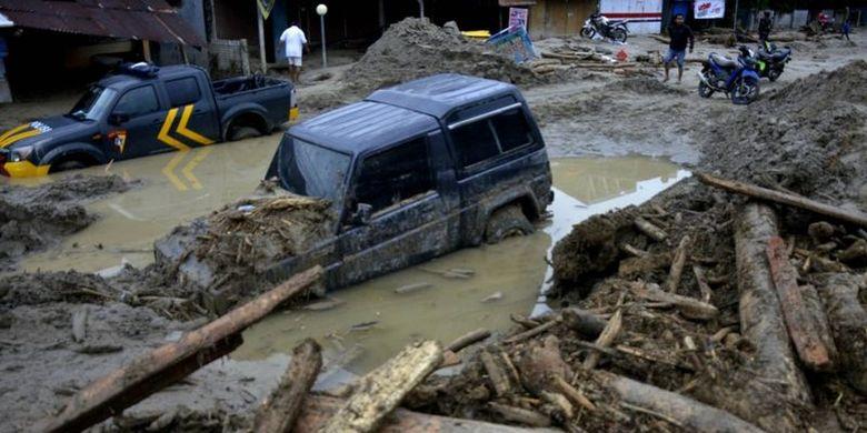 Kondisi rumah dan mobil yang tertimbun lumpur akibat terjangan banjir bandang di Kecamatan Masammba, Kabupaten Luwu Utara, Sulawesi Selatan, Rabu (15/07). Setelah banjir bandang melanda, beberapa warga menyaksikan banyaknya potongan kayu besar memenuhi sungai.
