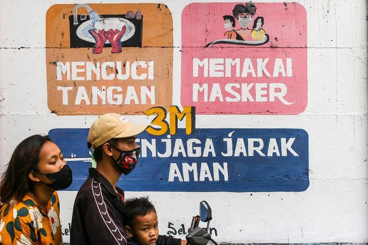 Pengendara melintas di dekat mural bertemakan COVID-19 di Petamburan, Jakarta, Rabu (21/7/2021). ANTARA FOTO/Rivan Awal Lingga/foc.