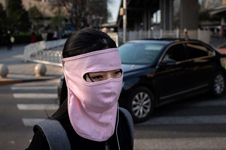 Seorang wanita mengenakan masker kain yang menutupi hampir seluruh wajahnya di tengah wabah virus corona (Covid-19) saat berjalan di luar gedung perkantoran di Beijing, China, Rabu (1/4/2020).