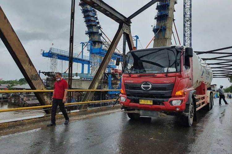 Terlihat truk pengangkut bahan bakar minyak (BBM) Pertamina sedang melintasi salah satu jembatan di Kalimantan Selatan (kalsel). Pertamina memastikan stok BBM dan LNG di Kalsel aman meski dilanda banjir bandang