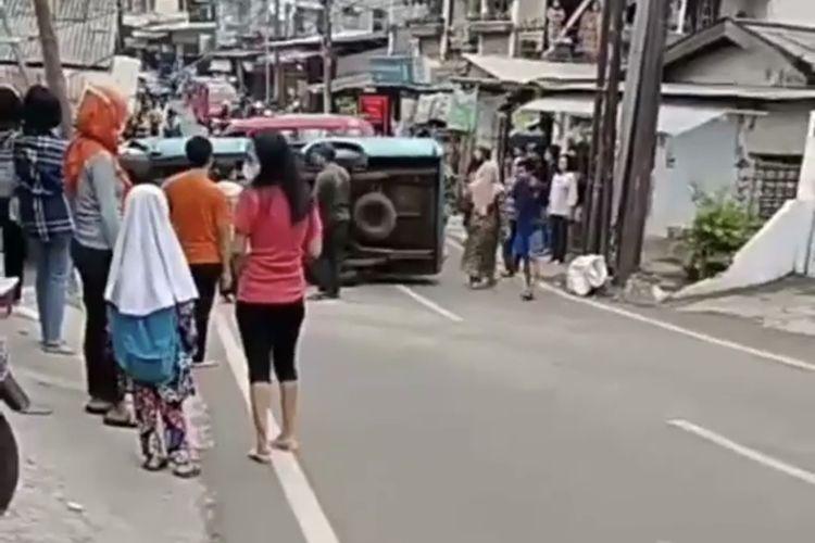 Sebuah angkutan umum (angkot) nomor 83 jurusan Tanah Baru - Lenteng Agung via Srengseng Sawah terguling di turunan Jalan Raya Jagakarsa dekat Pasar Lenteng Agung, Jagakarsa, Jakarta Selatan pada Rabu (23/6/2021) sore.