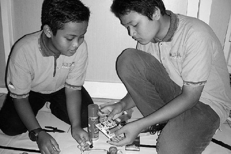 Dua siswa SMP Muhammadiyah 12 Gresik, Kota Baru, Kabupaten Gresik, Jawa Timur, Rizky Ramadani Putra (kiri) dan Rizieq Muhammad Minsuisnaen Maulidi (kanan) mencoba robot untuk melewati lintasan yang dibuat, Senin (8/5). Robot tersebut telah mendapatkan medali emas pada Olimpiade Al Quran, Seni, dan Teknologi (OLYQ) ke-3 di Bandung pada 26-27 April. Olimpiade ini diikuti peserta dari Indonesia, Malaysia, Thailand, dan Singapura.
