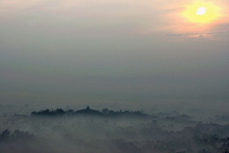 Mengamati matahari terbit di Punthuk Setumbu dengan latar candi Borobudur tertutup kabut.