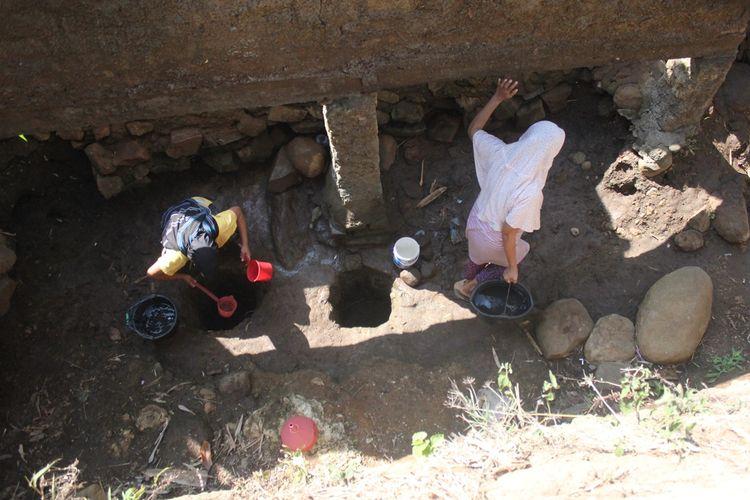 Warga di Cianjur, Jawa Barat memanfaatkan lubang-lubang tanah di dasar kolam yang mengering untuk mendapatkan air bersih akibat kemarau panjang yang melanda.