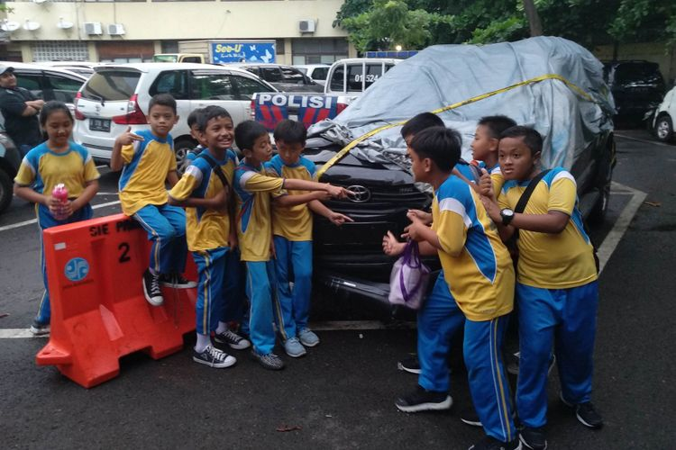 Anak-anak SD berfoto dengan Fortuner yang kecelakaan saat membawa Setya Novanto