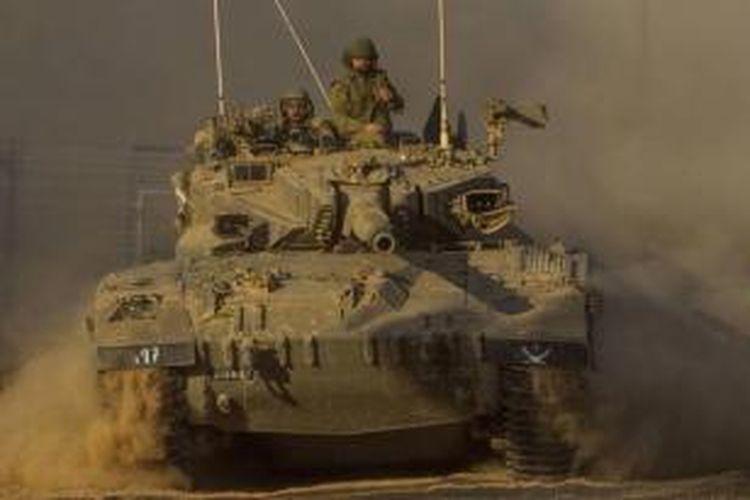 Sebuah tank Merkava milik Israel berpatroli di perbatasan Israel dan jalur Gaza, menyusul serangan udara yang dilancarkan Israel ke Palestina, 10 Juli 2014. Serangan Israel ke kota Gaza menewaskan puluhan warga Palestina termasuk wanita dan anak-anak.