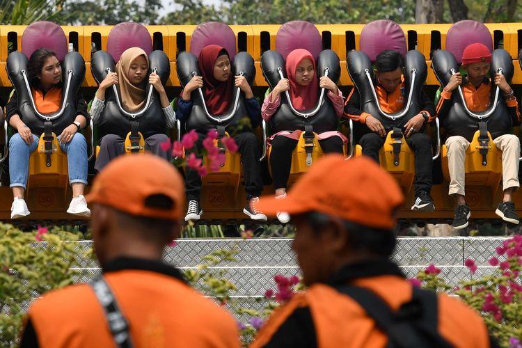 Sejumlah petugas Penanganan Prasarana Sarana Umum (PPSU) DKI Jakarta mencoba wahana permainan saat berwisata di Dufan, Ancol, Jakarta, Senin (22/7/2019). Wisata gratis bagi 20 ribu petugas PPSU tersebut  sebagai bentuk penghargaan kepada petugas yang telah menjaga kebersihan Ibu Kota.