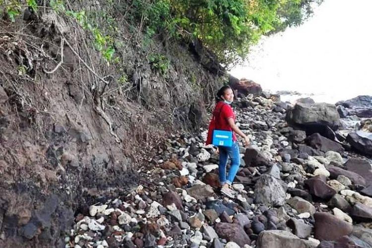 Saat Maria Mahendra Charolin (28), seorang perawat yang bertugas di Pulau Palue, Kabupaten Sikka, NTT menyusuri jalan berbatu menuju rumah rumah warga.