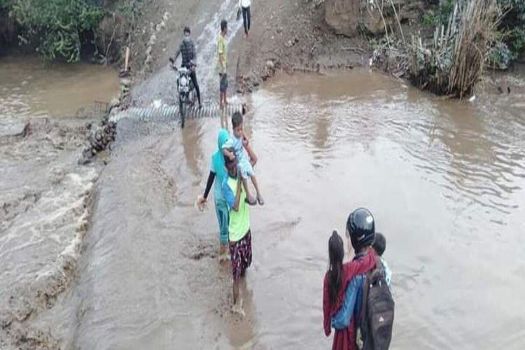 Warga harus bertaruh nyawa menyeberangi derasnya arus sungai lantaran tak adanya jembatan penghubung. Bahkan, para pengendara harus meminta warga sekitar untuk memikul kendaraan sampai keseberang sungai.