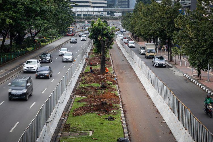 Kendaraan melintas di samping pohon-pohon yang telah ditebang di Jalan Sudirman, Jakarta, Sabtu (10/3/2018). Sebanyak 541 pohon di sepanjang jalan thamrin-sudirman ditebang imbas penataan trotoar yang akan dimulai oleh pemprov DKI Jakarta.