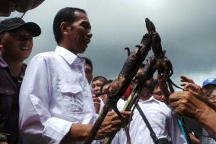 Bakal capres PDI Perjuangan Joko Widodo disodori tikus bakar saat mengunjungi Pasar Tomohon, Sulawesi Utara, dalam rangka safari politik, Sabtu (10/5/2014).