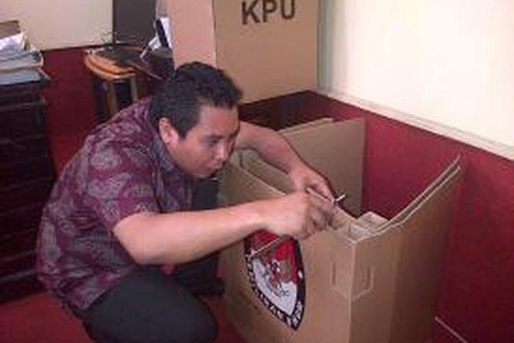 Ketua KPU Sultra mengukur ketebalan bilik suara yang terbuat dari kardus yang tak sesuai spesifikasi, padahal logistik itu akan digunakan pada pemilu 2014 mendatang