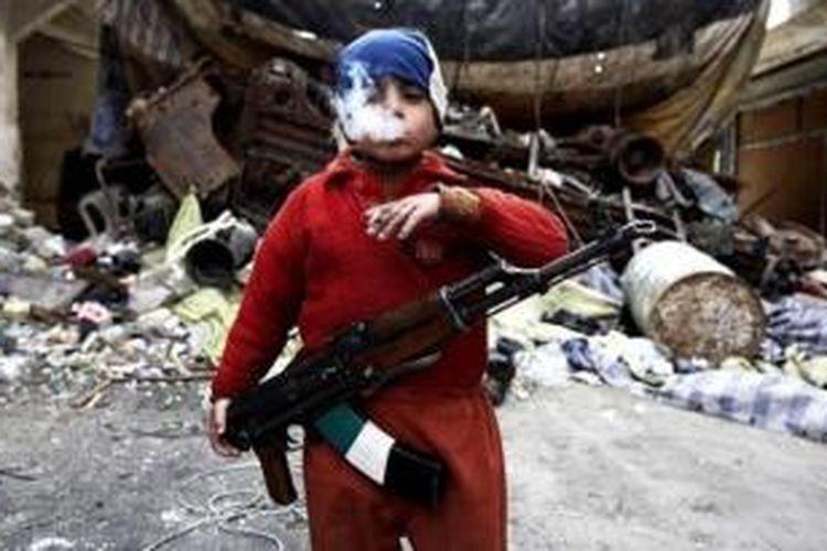 Dalam foto ini terlihat Ahmed (7) menyandang sebuah senapan serbu AK-47 sambil merokok di depan sebuah kubu perlindungan pemberontak di kota Aleppo, Suriah.