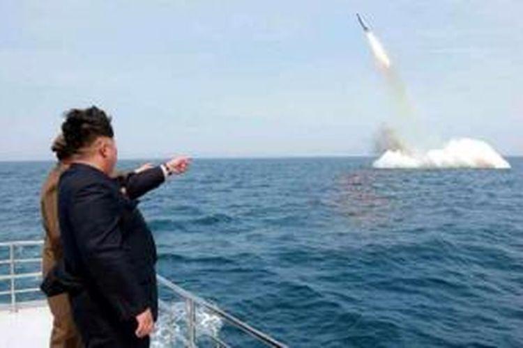 Pemimpin Korea Utara Kim Jong Un menyaksikan peluncuran sebuah misil balistik dari kapal selam di perairan dekat Sinpo, di timur laut negeri itu. Militer AS mengklaim foto ini adalah foto palsu yang direkayasa demi kepentingan propaganda.
