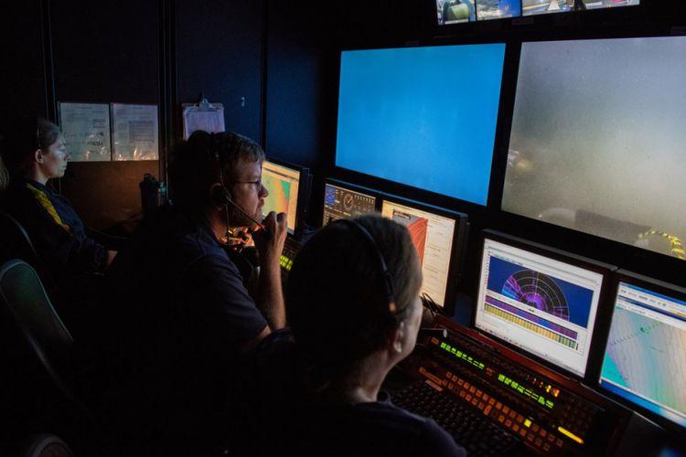 Para ahli mengendalikan dan memantau penyelaman kapal di E / V Nautilus yang sedang menelusuri dasar laut untuk mencari sampel meteroit.