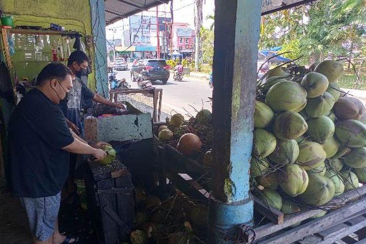 Penjual kepala muda sedang menyiapkan dagangannya untuk pelanggan. Penjualan kelapa muda meningkat lantaran diyakini bisa tangkal efek vaksin Covid-19.  Pembelinya kebanyakan warga yang usai melaksanakan vaksinasi.
