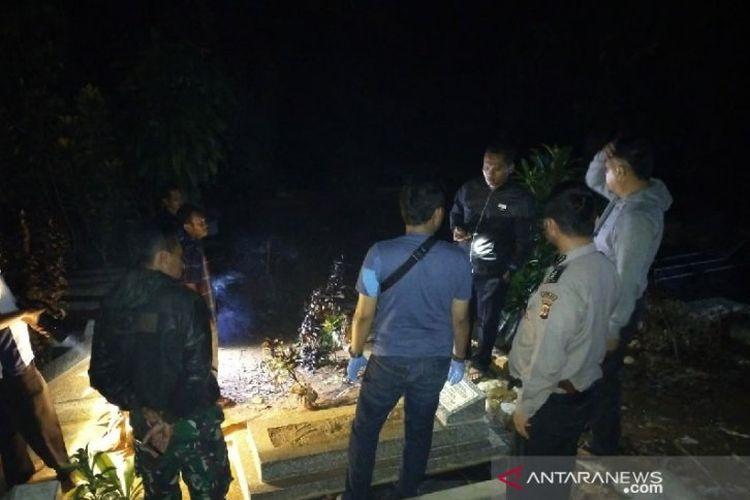 Polisi dan warga memeriksa kondisi makam yang rusak di Tempat Pemakaman Umum Kampung Pakemitan, Kecamatan Cikatomas, Kabupaten Tasikmalaya, Jawa Barat, Jumat (8/11/2019). ((ANTARA/HO Polsek Cikatomas))