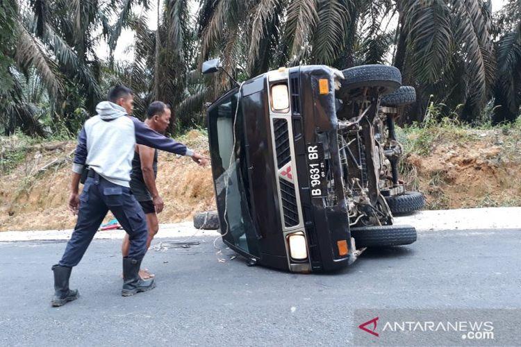 Warga berada di sekitar mobil yang mengalami kecelakaan di Kawasan Bukit Lantak Nagari Tabek, Kabupaten Dharmasraya, Rabu (26/6).