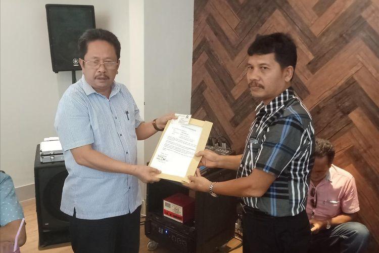 Pendiri Perindo Sumbar HM Tauhid (kiri) menyerahkan surat pengunduran dirinya kepada kepala sekretariat Perindo Sumbar, Zubir, Kamis (4/7/2019)